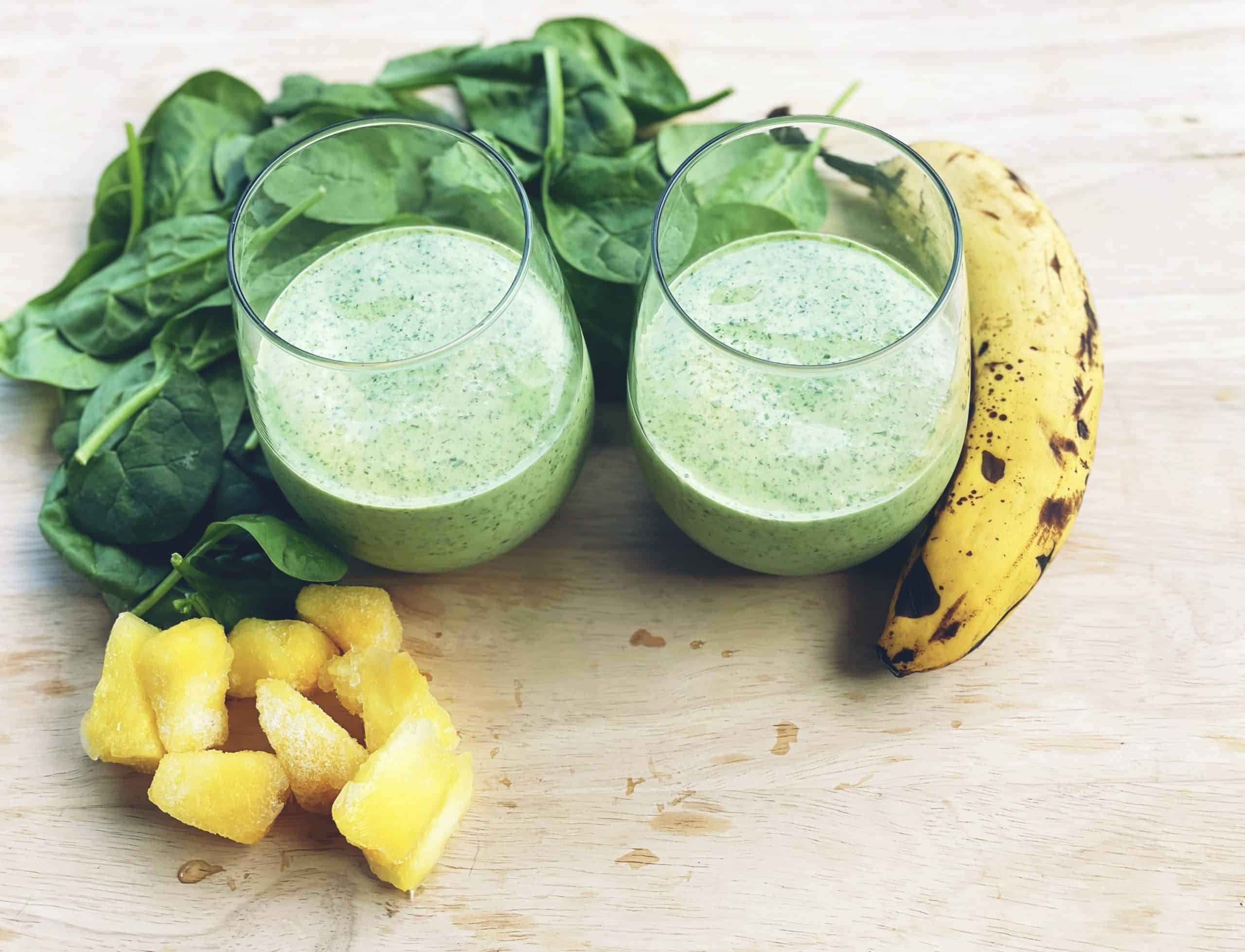 2 glasses with island green smoothie surrounded by banana, spinach and pineapple