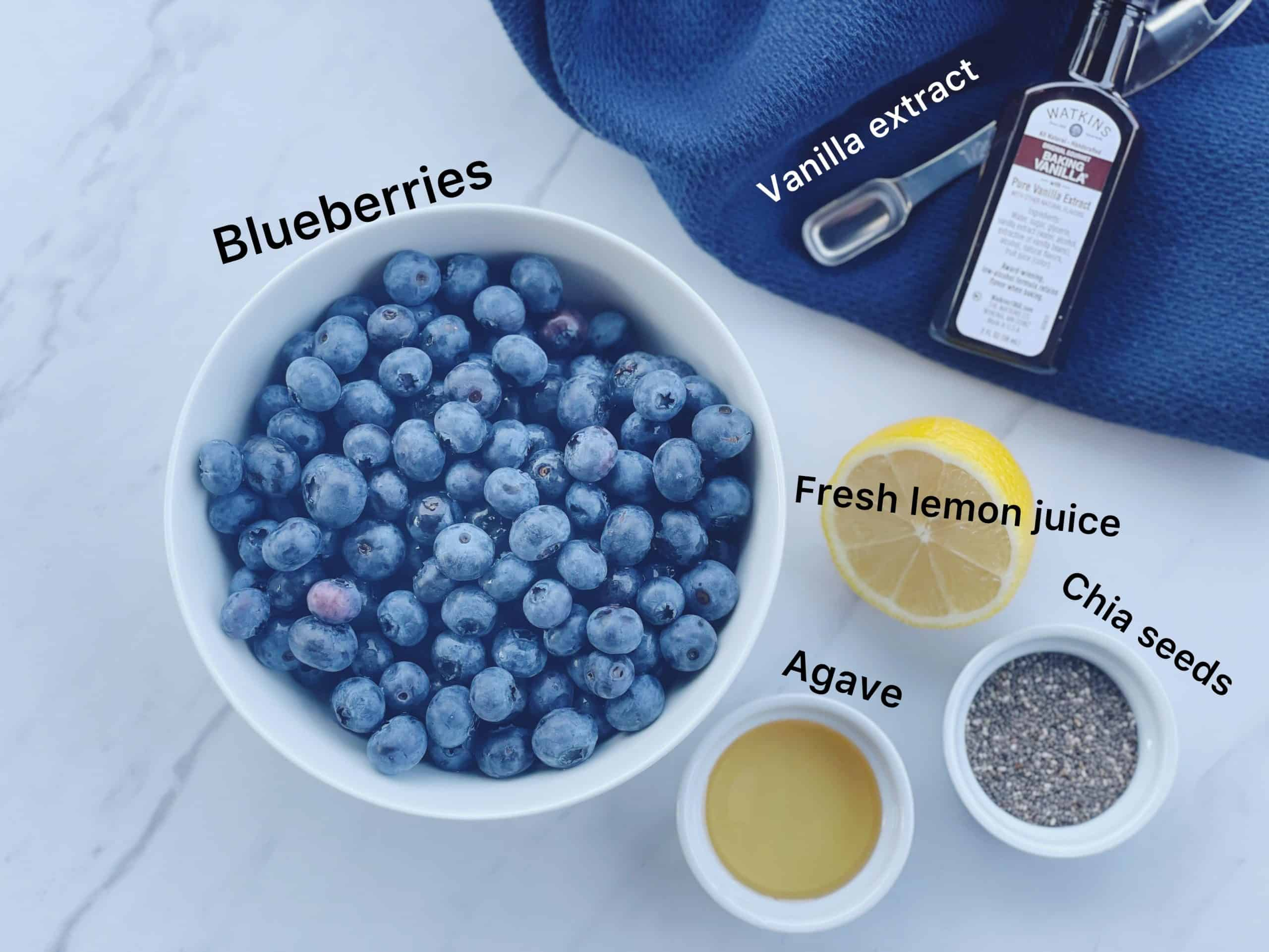 ingredients for blueberry chia jam, including blueberries, lemon juice, agave, vanilla extract and chia seeds