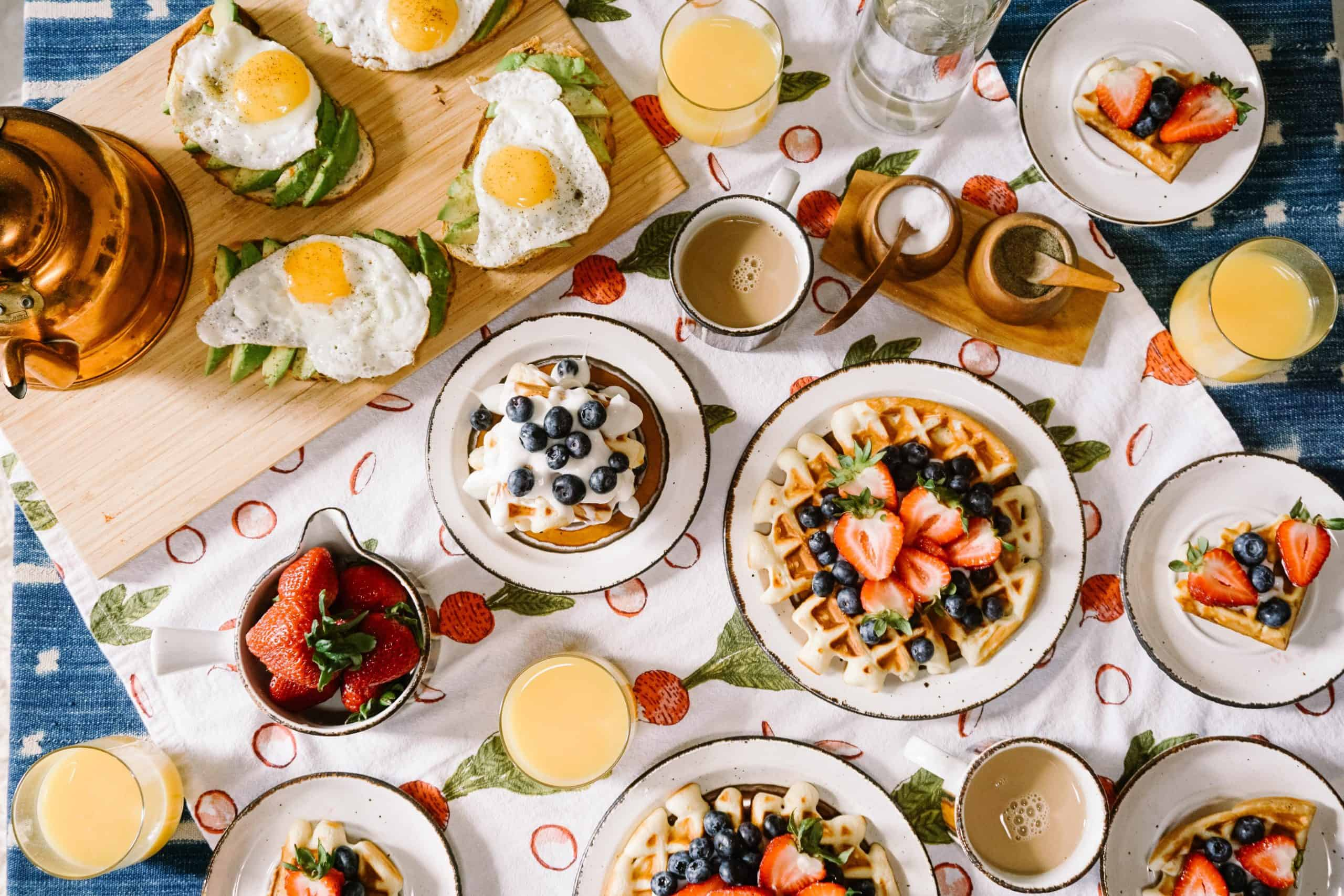 table with breakfast items spread across, like eggs, waffles, mimosas