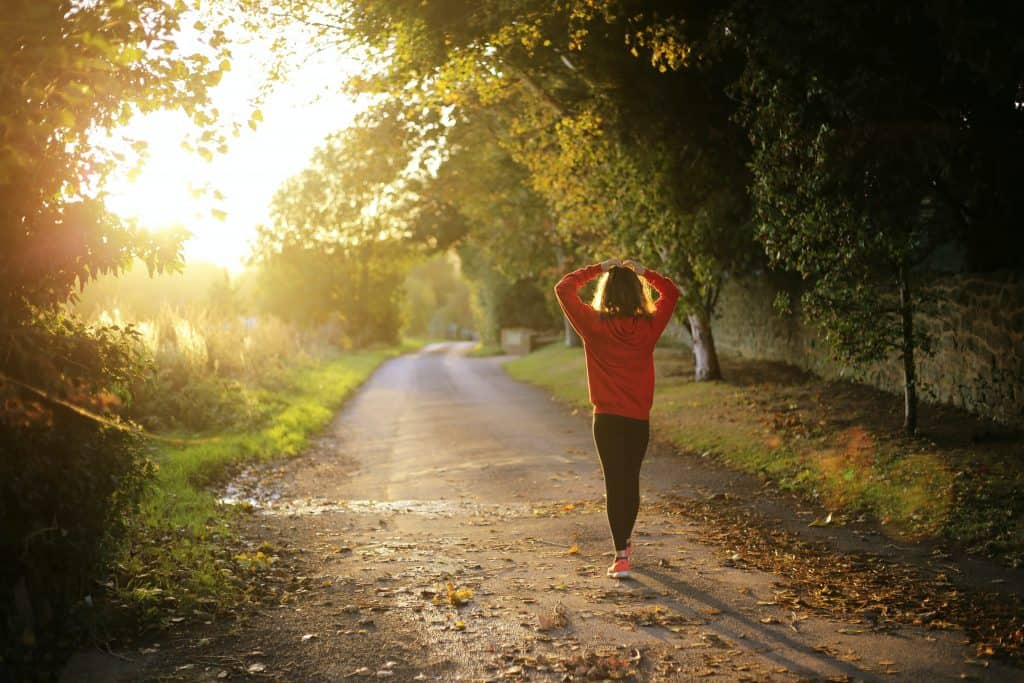 How can you optimize your physical health. Woman walking on trail in the sunlight surrounded by trees