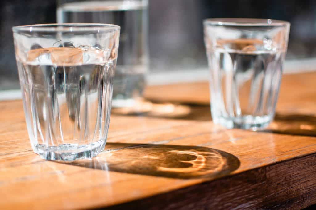 cups of water sitting on wooden table in sunlight