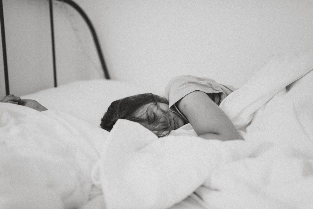 woman sleeping in bed with white comforter